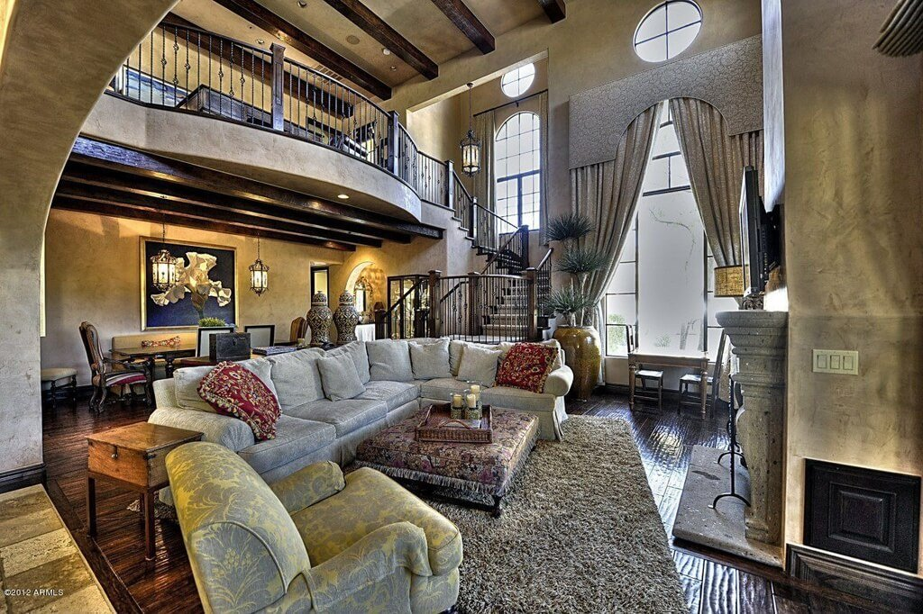 Lavish detail abounds in this stately living room, from enormous drapes over the two story windows, to upper floor balcony with dark wood trim, to expansive sectional and massive ottoman standing before a great stone fireplace. Dining area sits beneath exposed wood beams under the balcony, next to curved staircase.