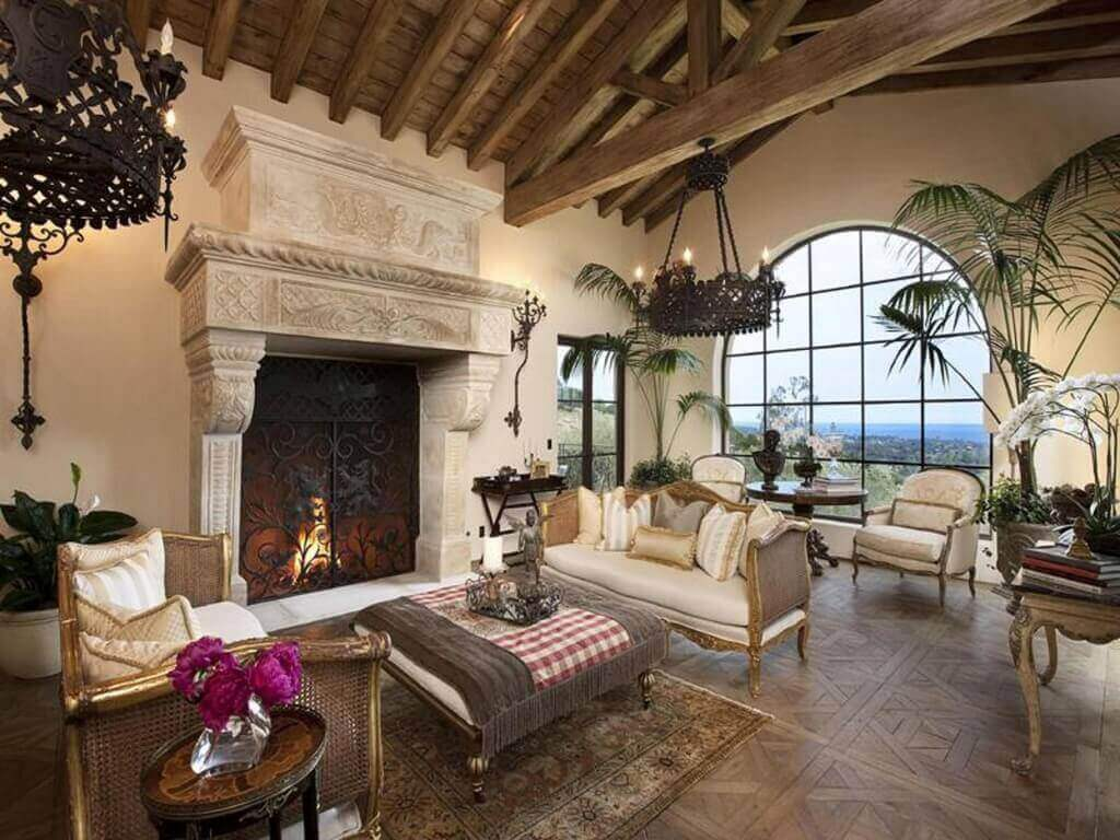 Living room combining stately traditional look with tropical, open feel. Soaring exposed beams stand above patterned wood flooring, with immense carved marble fireplace standing near ornate carved traditional sofas and massive combination ottoman and coffee table.