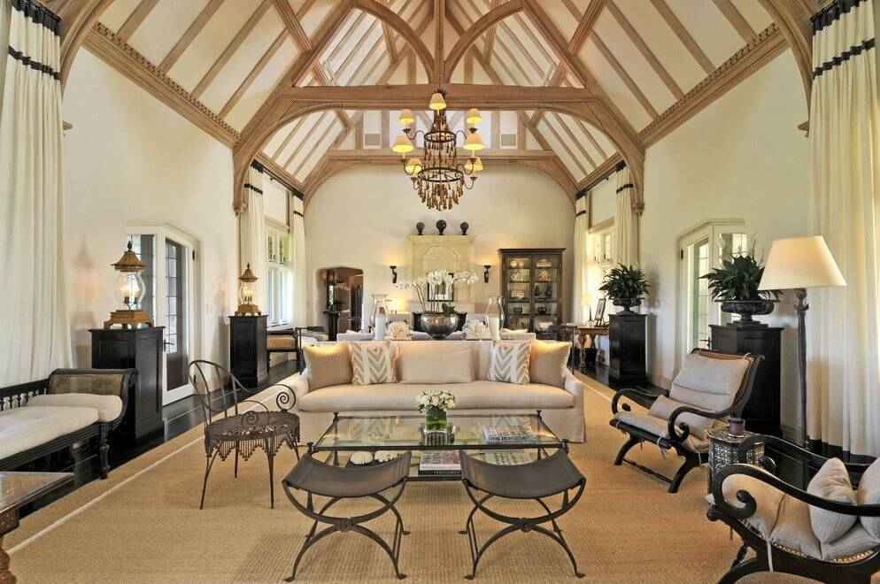 Delicately balanced living room stands light and dark furniture over sprawling beige area rug on dark wood floor, beneath vaulted white ceiling with natural wood exposed beams.