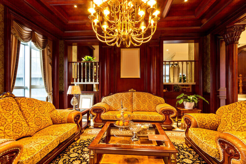 Lush cherry wood bedecks every wall surface int his living room, with a trio of ornate, camel back, patterned cushion sofas standing around large polished wood and glass coffee table.