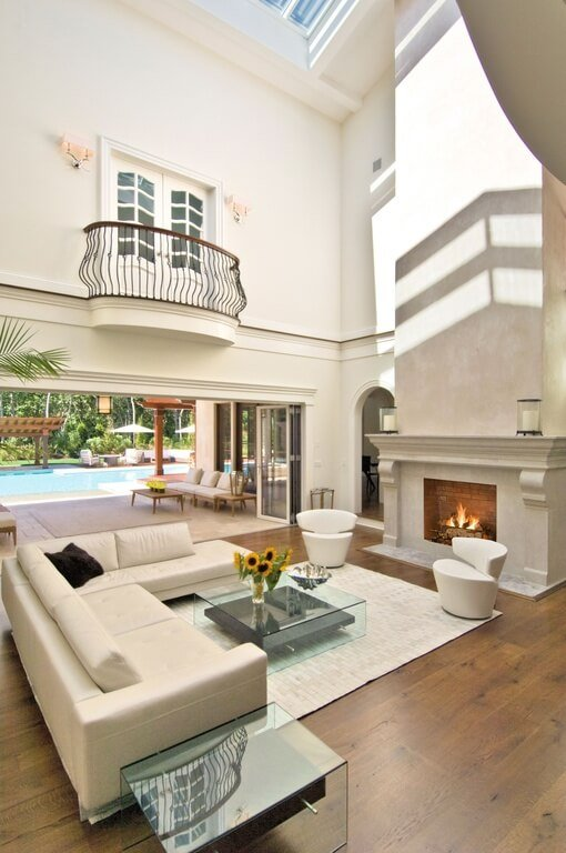 Vaulted ceiling with skylight windows illuminates this living room with natural hardwood flooring and beige leather sectional, all-glass tables and large fireplace standing next to retractible, fully open patio entrance.