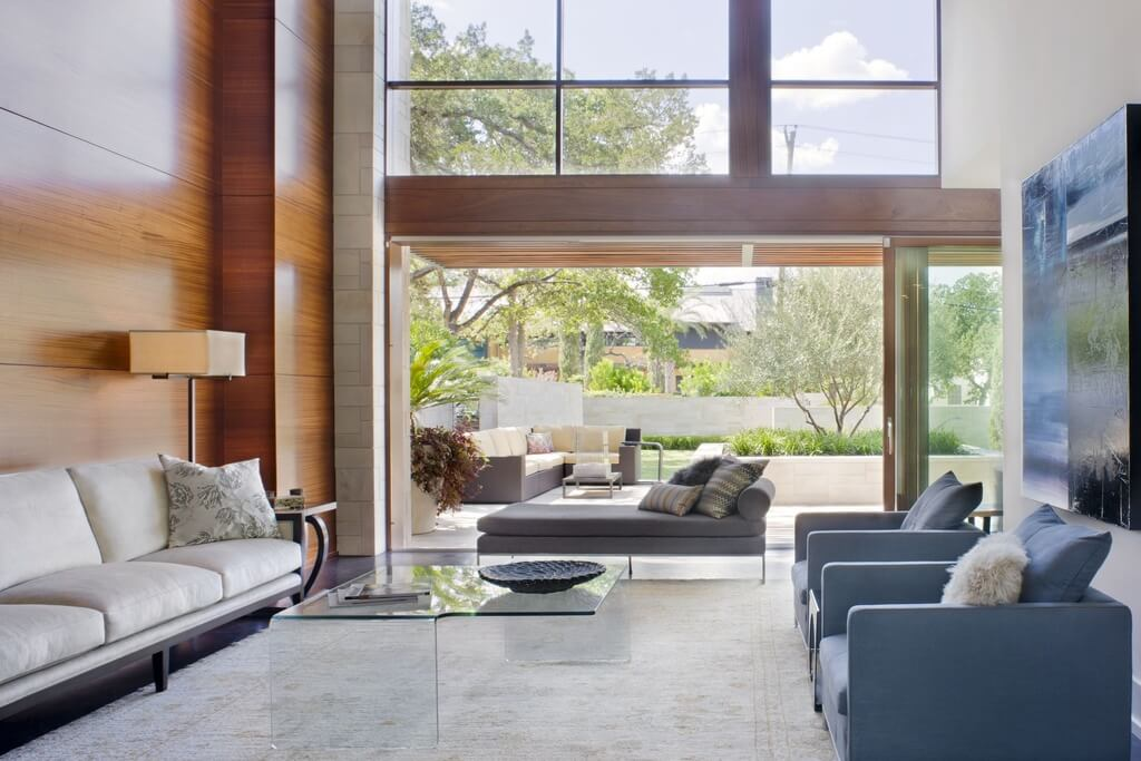 Lush tones throughout this living room, fully open to the patio by sliding glass panels, include blue armchairs, fully glass coffee table, hardwood and brick walls, and large white rug over dark hardwood flooring.