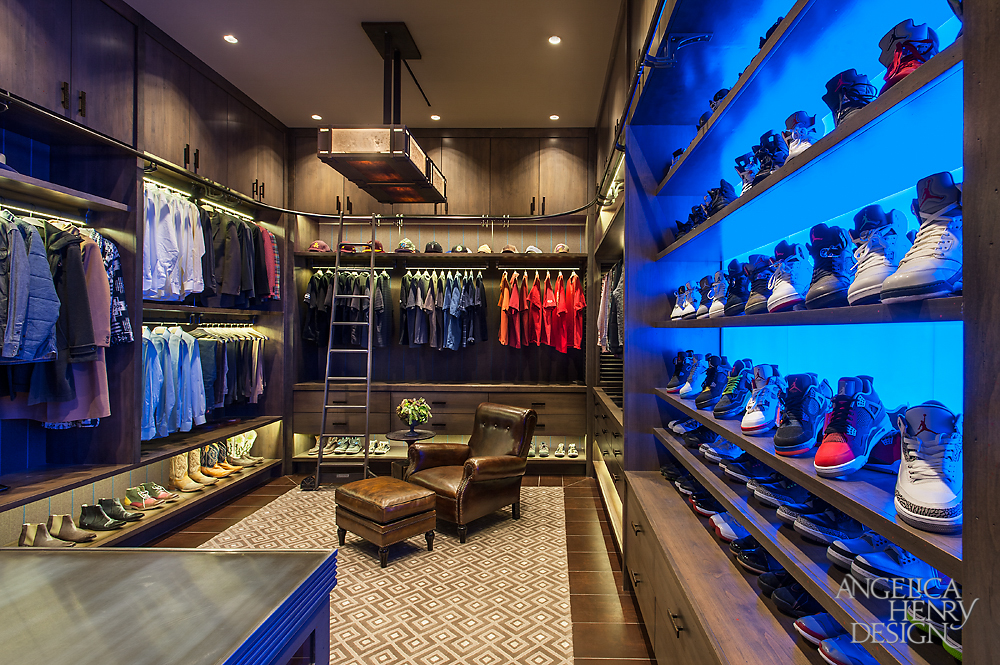 """Image of the entire """"his"""" luxury walk-in-closet with extensive footwear storage, suit racks and brown leather armchair."""