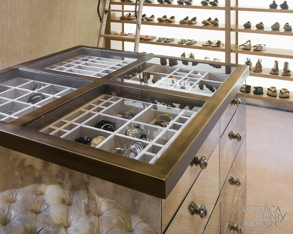Custom dresser drawers in her luxury walk-in-closet surrounded by extensive footwear shelving.