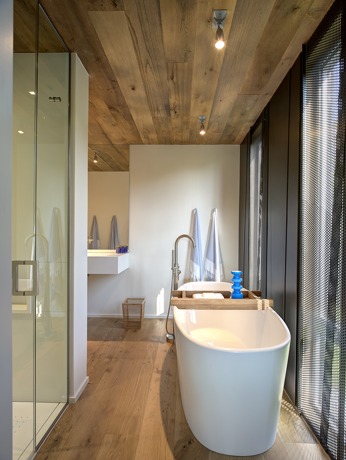 """White pedestal tub sits next to perforated metal exterior wall shade in primary bath, fearing glass door walk-in shower and another """"floating"""" white slab countertop."""