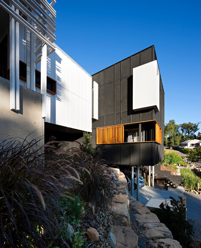 """Here we see the """"charred box"""" design protruding from the hillside, hovering over paring space with the help of metal supports. The tiered rock surfaces gently raise the surrounding yard along with the natural slope."""
