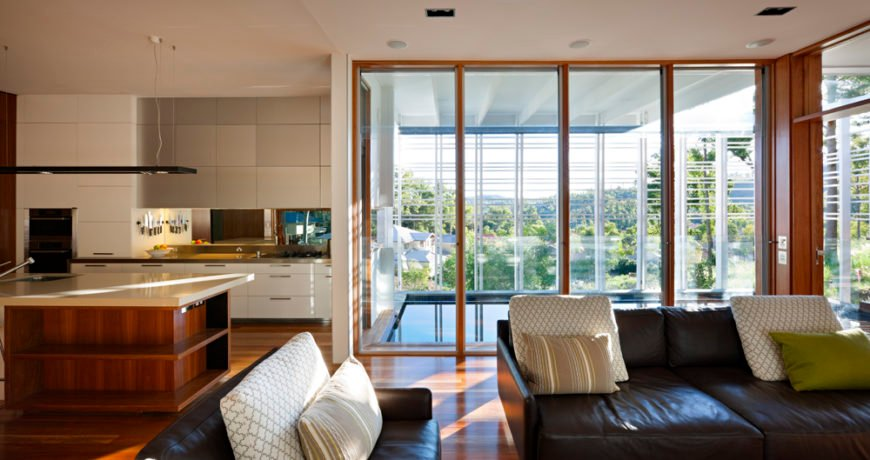 Within the main open space we see the living room flowing into the kitchen area, with floor to ceiling external glass affording wide views outdoors.