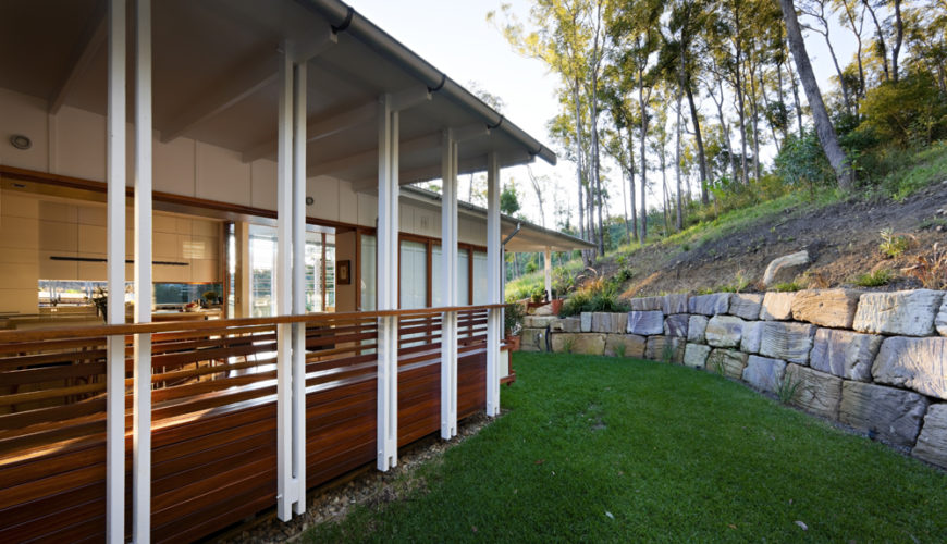 The rear of the home, on the top floor, meets up at ground level as the hill rises. Large carved stone retaining wall carves out a grassy yard space, while rich hardwood patio with built-in seating extends from the open central area of the home.