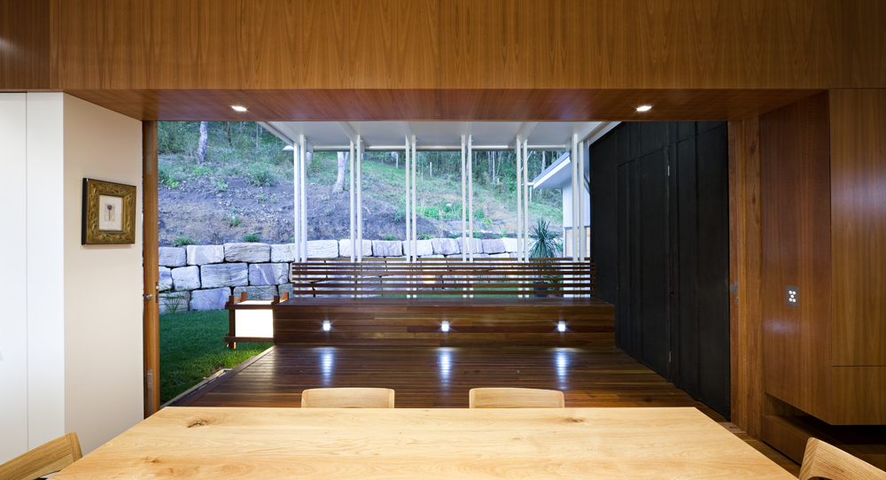 View from the kitchen over dining room table showcases the lush natural wood cabinetry and wall surfaces, open hardwood patio, and upward slope of the land.