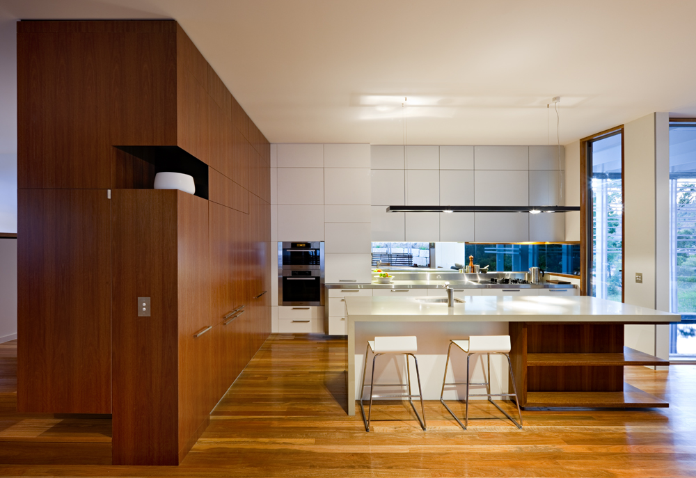 The kitchen is awash in the contrast of natural wood and glossy white surfaces, exemplified by the large white and wood island with built-in shelving and dining space. Minimalist cabinetry design complements wood paneling at left.