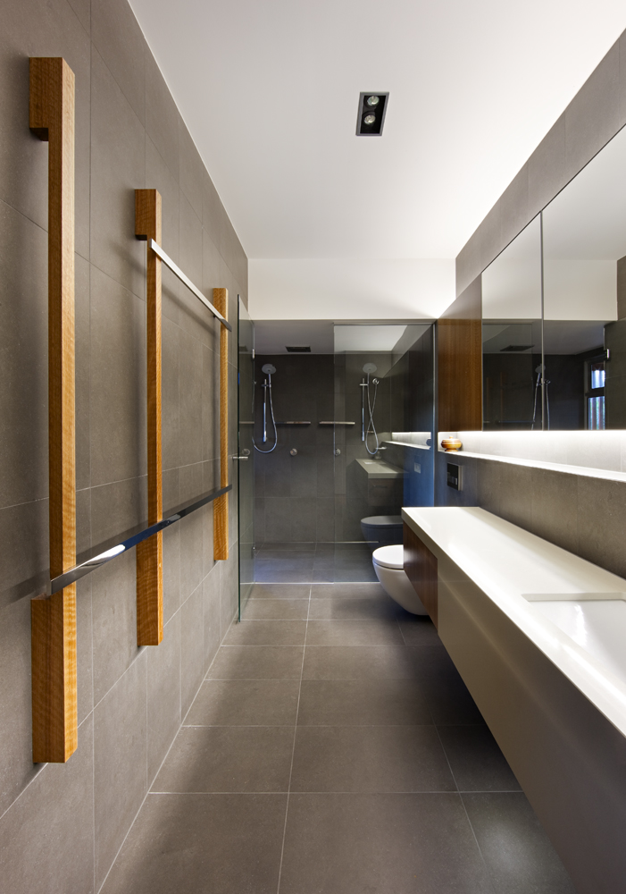 Ultra modern bathroom features continuous white slab countertop and built-in, under-lit wall shelving strip beneath mirrors and cabinetry. Glass door shower flows seamlessly.