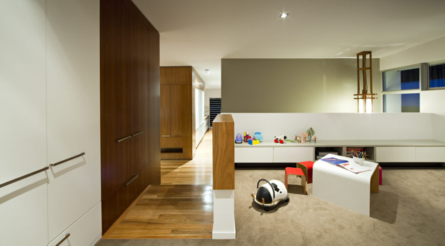 On the right of the central hallway is this children's space, with white low-slung wall divide holding built-in storage for playthings and soft beige carpeting.