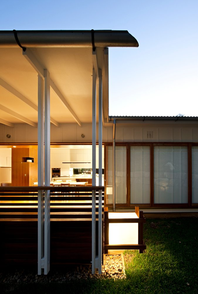 Rear of the home as seen at night. Unique light cube in natural wood frame illuminates the patio space, in front of expanse of sliding glass.
