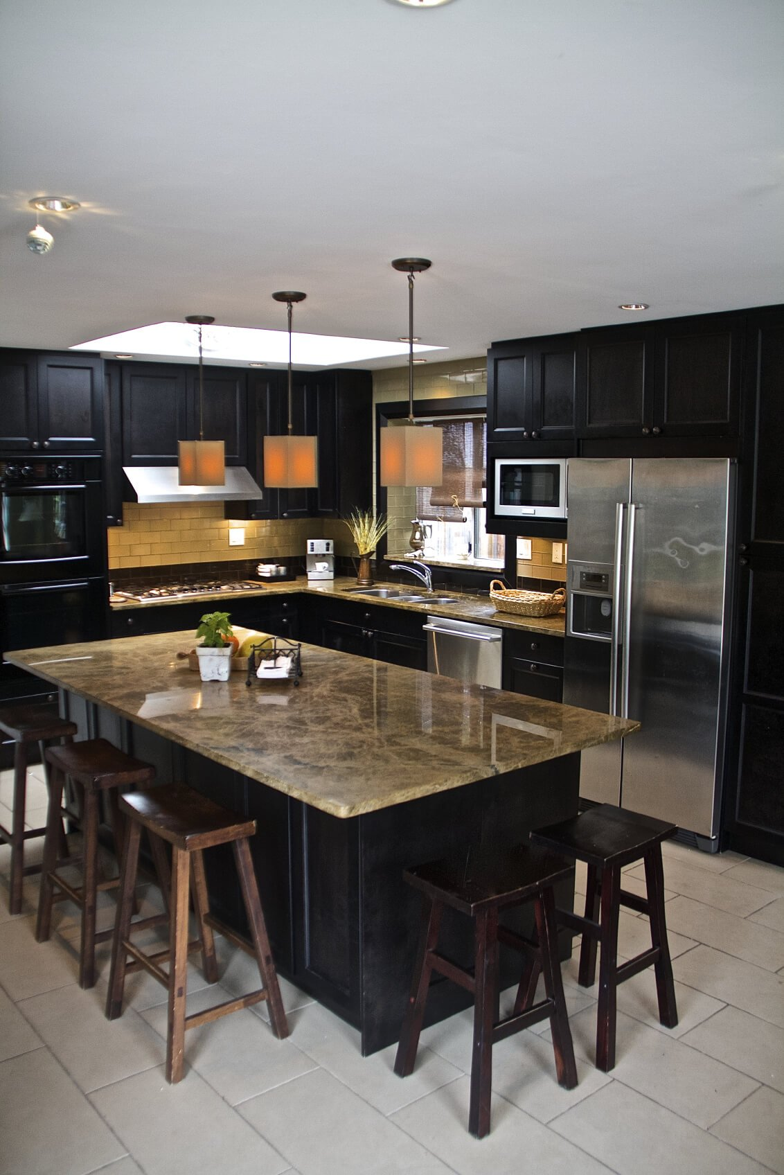 Contemporary black L-shaped kitchen with long island set on white tile floor.