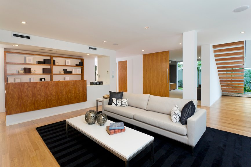 High contrast living room pits black area rug and beige contemporary leather sofa against light natural wood flooring, shelving, doors, and stairs mounted on pure white walls and ceiling.