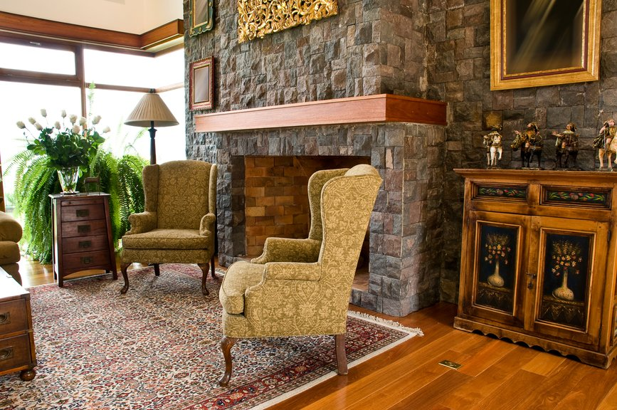 Lush textures define this cozy living room. Stone fireplace surround extends to entire wall, with rich natural wood mantle above. Natural hardwood flooring is nearly matched with cabinetry and drawer-equipped coffee table, while twin high back chairs join on patterned area rug at center.
