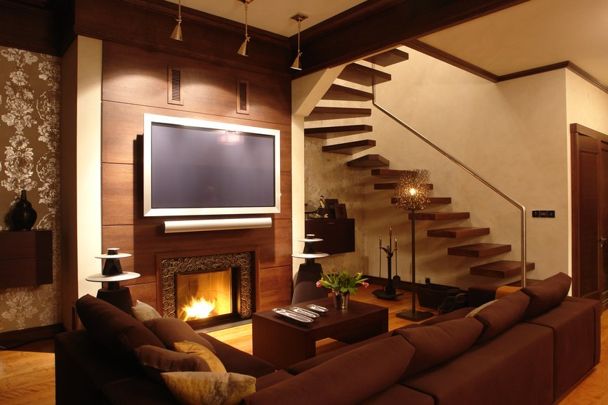 Modern styled living room sets dark brown sectional and wood coffee table before fireplace with sleek natural wood paneled surround. Dark 'floating' staircase at right matches accent tones throughout, including molding and door frames.