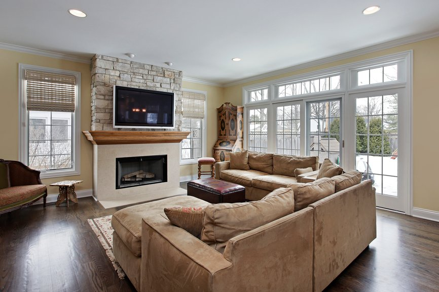 Dark hardwood flooring supports a pair of light mocha sofas in this living room featuring a marble and stone fireplace surround, with all glass patio doors at right.