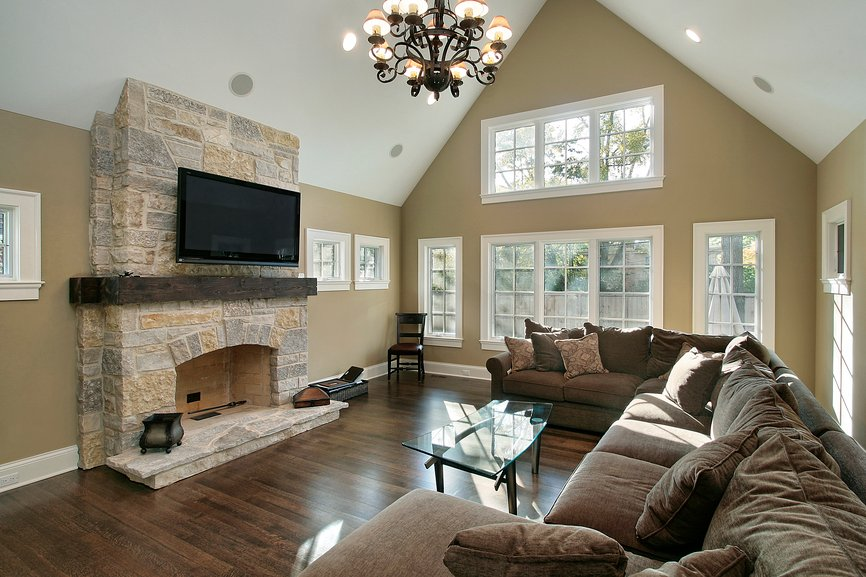 Vaulted ceiling and sculpted metal chandelier hang above a wide expanse of plush cushioned brown sectional, glass coffee table, and massive stone brick fireplace over dark natural hardwood flooring.