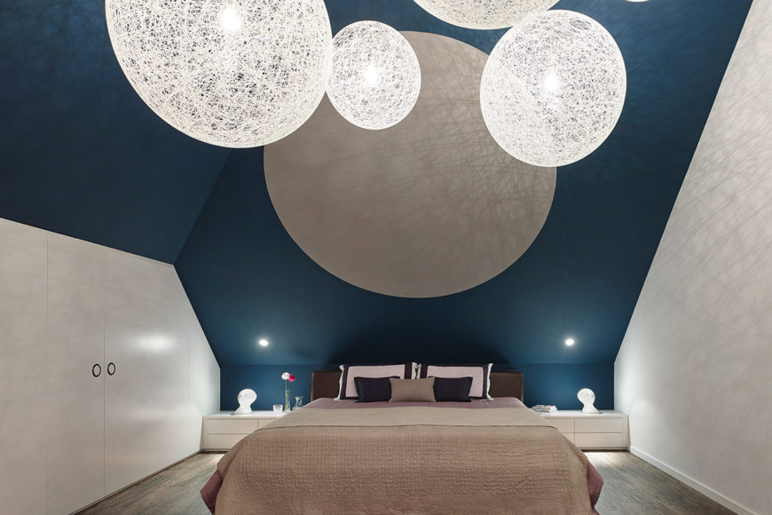 Soaring vaulted ceiling allows for constellation of chandelier spheres over the primary bed, with built-in shelving flanking both sides.