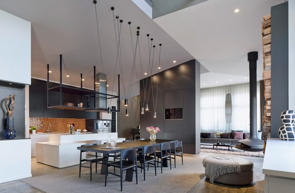 """Here is the open expanse at the center of the home, including living room in distance, large dining space in foreground, and kitchen on left. Angular cable-hung light canisters float above large dark wood dining table, while unique """"pod"""" fireplace hangs nearby."""