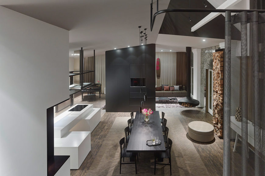 Overhead view of the dining space reveals the cubic structures throughout, including white countertops and central dividing wall in black. Floor to ceiling firewood stack on right provides practical and aesthetic addition.