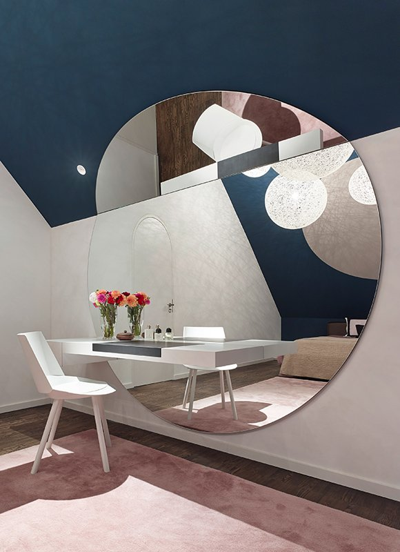 Bedroom vanity space features another floating element - counter is mounted directly to immense circular wall mirror for a hallucinatory effect. Arched doorway camouflaged in wall is seen in reflection.