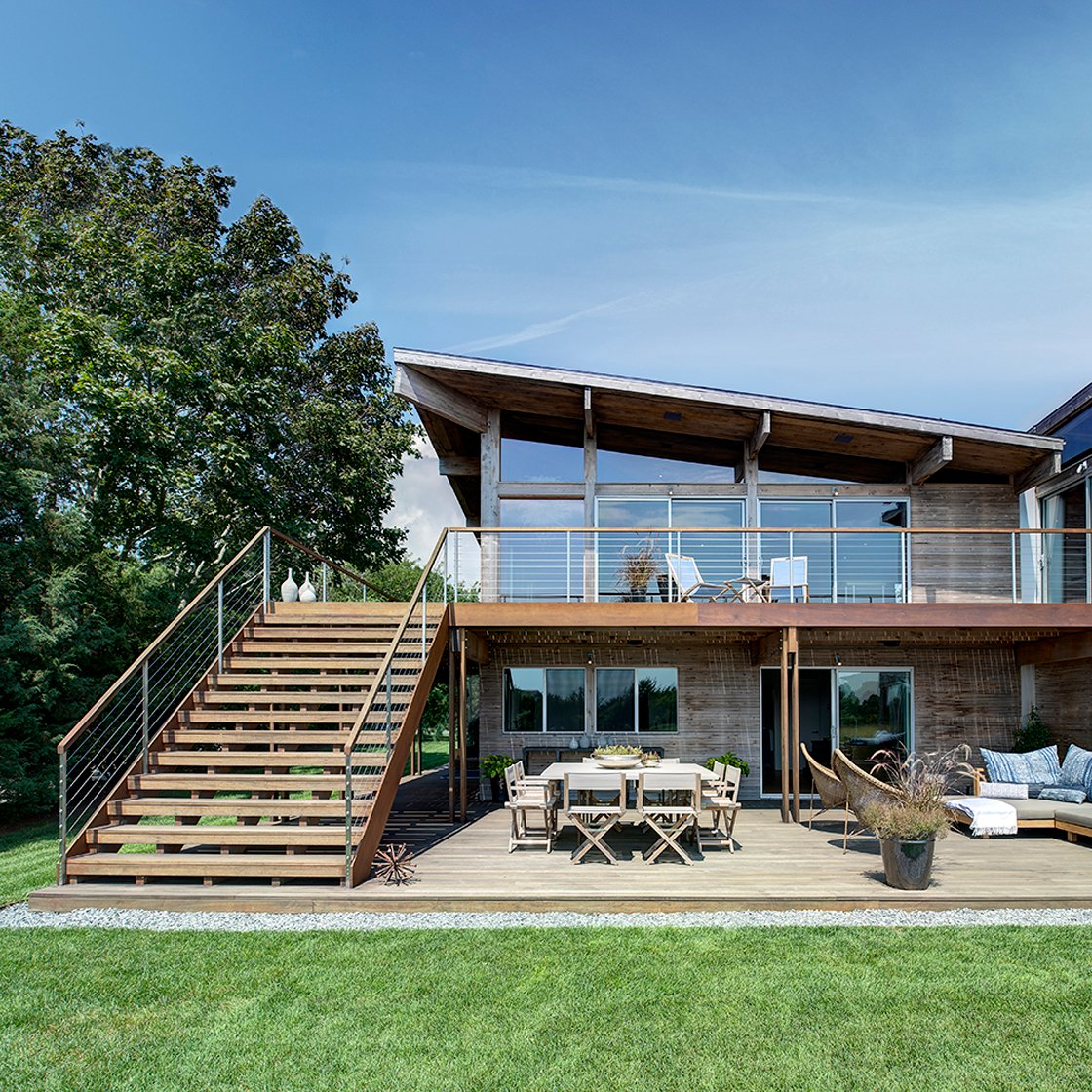 The rear of the home features an extensive lower patio on raised natural wood, allowing for sheltered seating beneath the balcony and a full dining area. Floor to ceiling glass on the upper level, with multiple sliding doors, allows for natural light and air to fill the home.