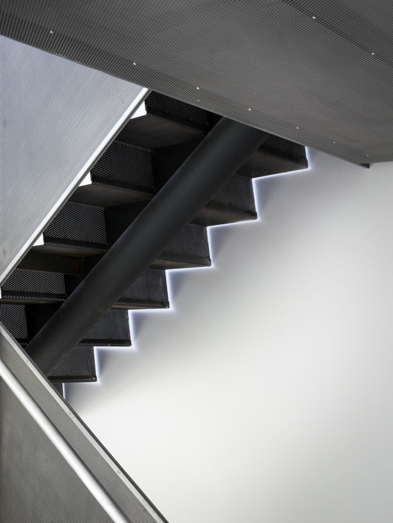 The black mesh metal staircase allows light through, while standing out in full contrast from the thoroughly white interior.