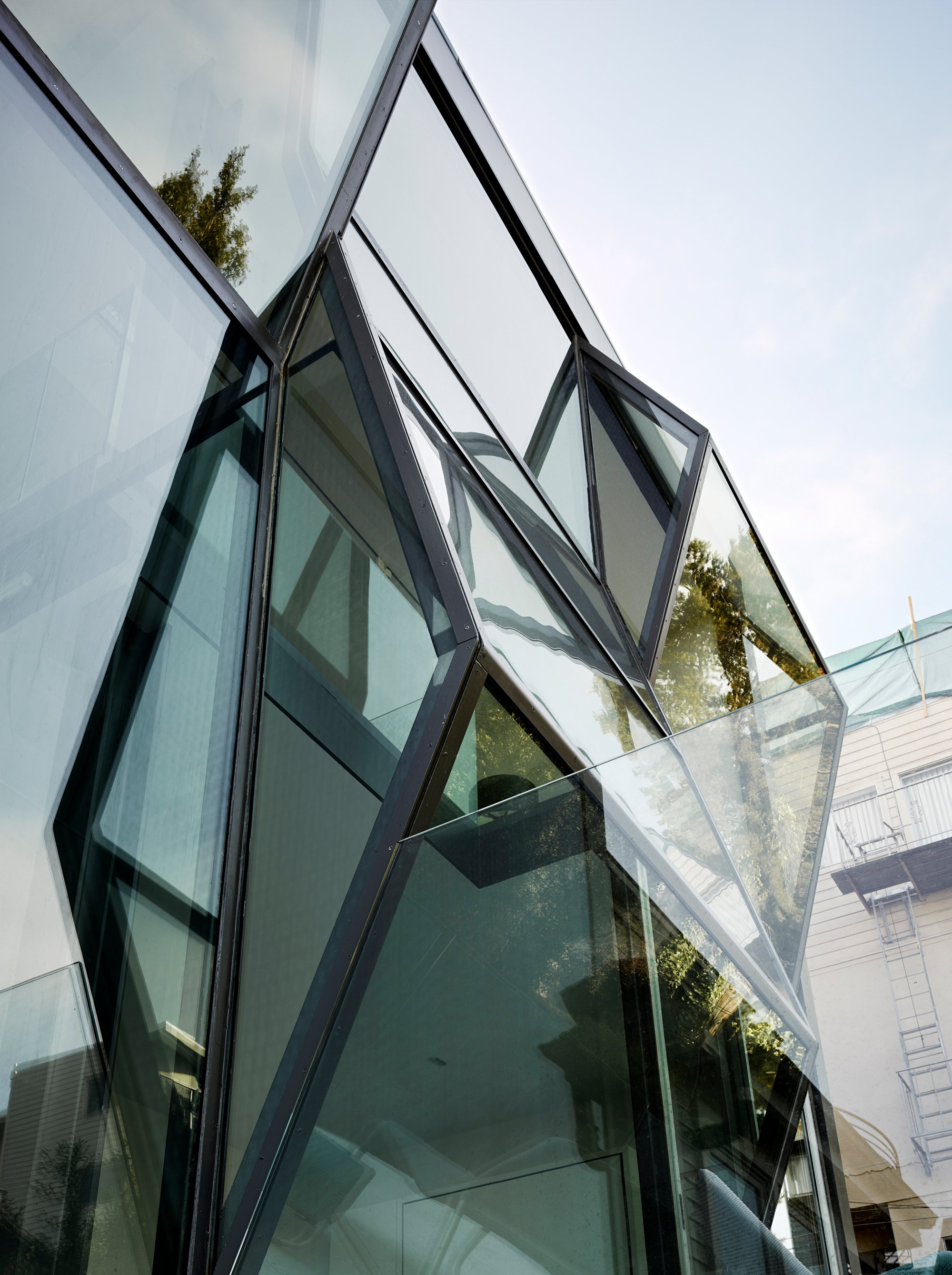 Finally, a few of the rear glass prism facade as seen from the ground level. Glass panels in multiple angles refract reflections of the surrounding nature, diffusing any flat surfaces.