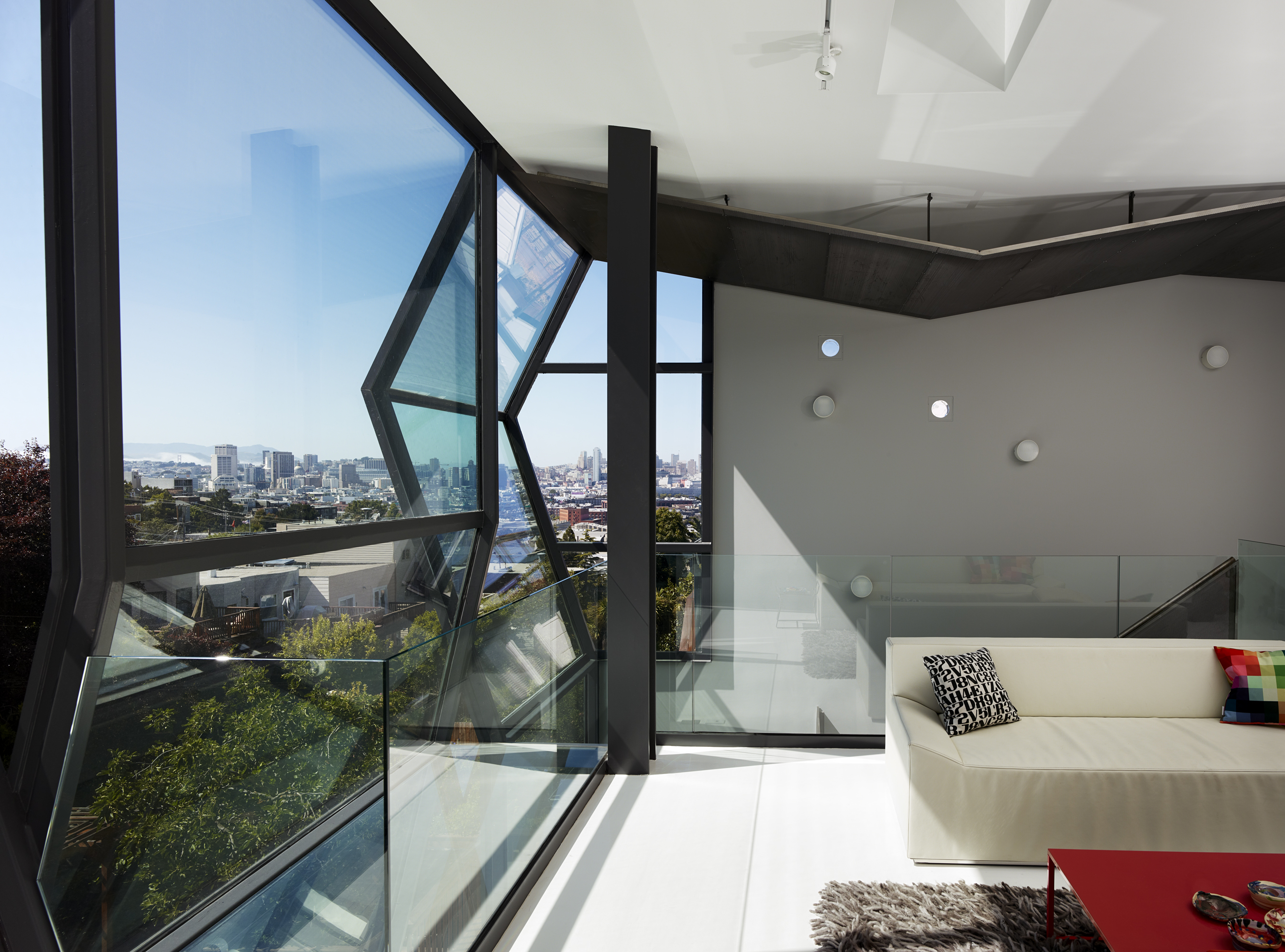 Here's a profile view of the back of the home, showcasing both the minimalist living room, with splashes of red and black, and the alternating prism shapes of the rear glass facade. Black sound dampener on the ceiling reflects the shape.