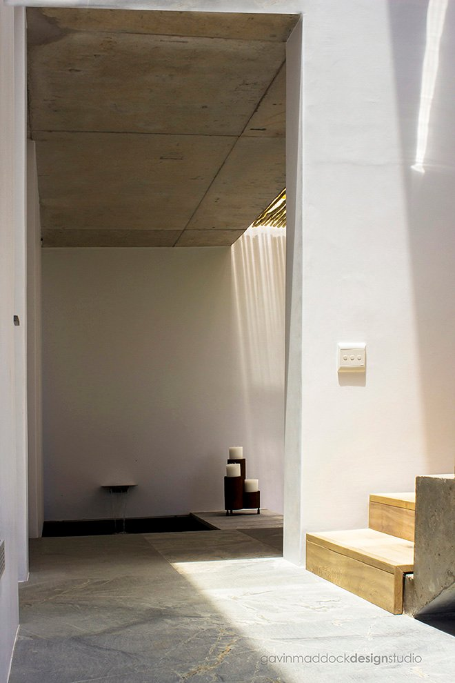 """The landing is where light hardwood stairs meet concrete flooring, with bamboo """"skylight"""" ceiling seen in background."""