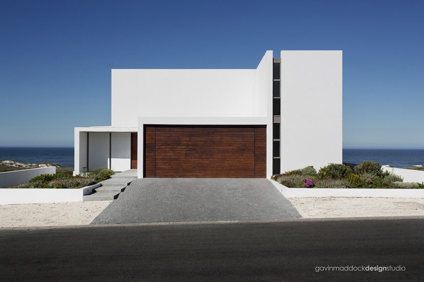 As seen from the street, the home conceals most of its details behind a broad swath of white, with only a vertical window strip and dark wood garage door breaking up the facade.