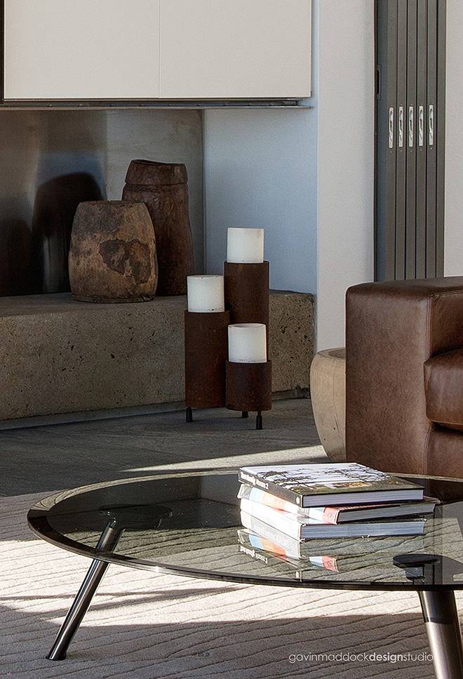 Close detail in the living room highlights the modern glass and steel coffee table and, in background, the retractible glass panels hidden within the wall.