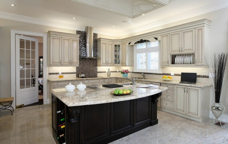 Kitchen with black island and white cabinets
