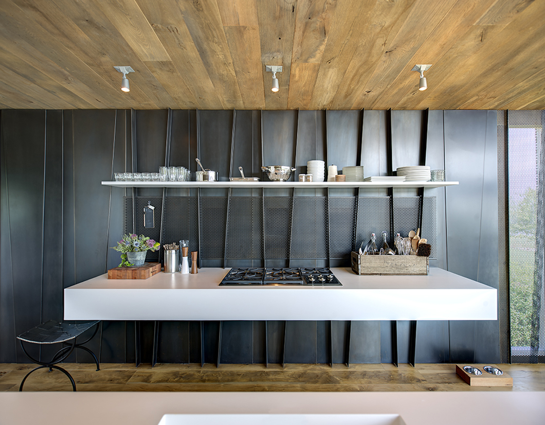 """The kitchen space features this striking white slab of """"floating"""" countertop attached to black metal wall, with built-in range."""