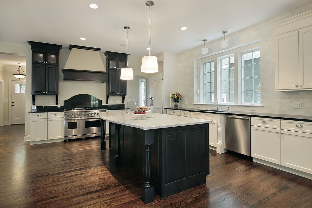 Large kitchen with black island and mix of black and white cabinets