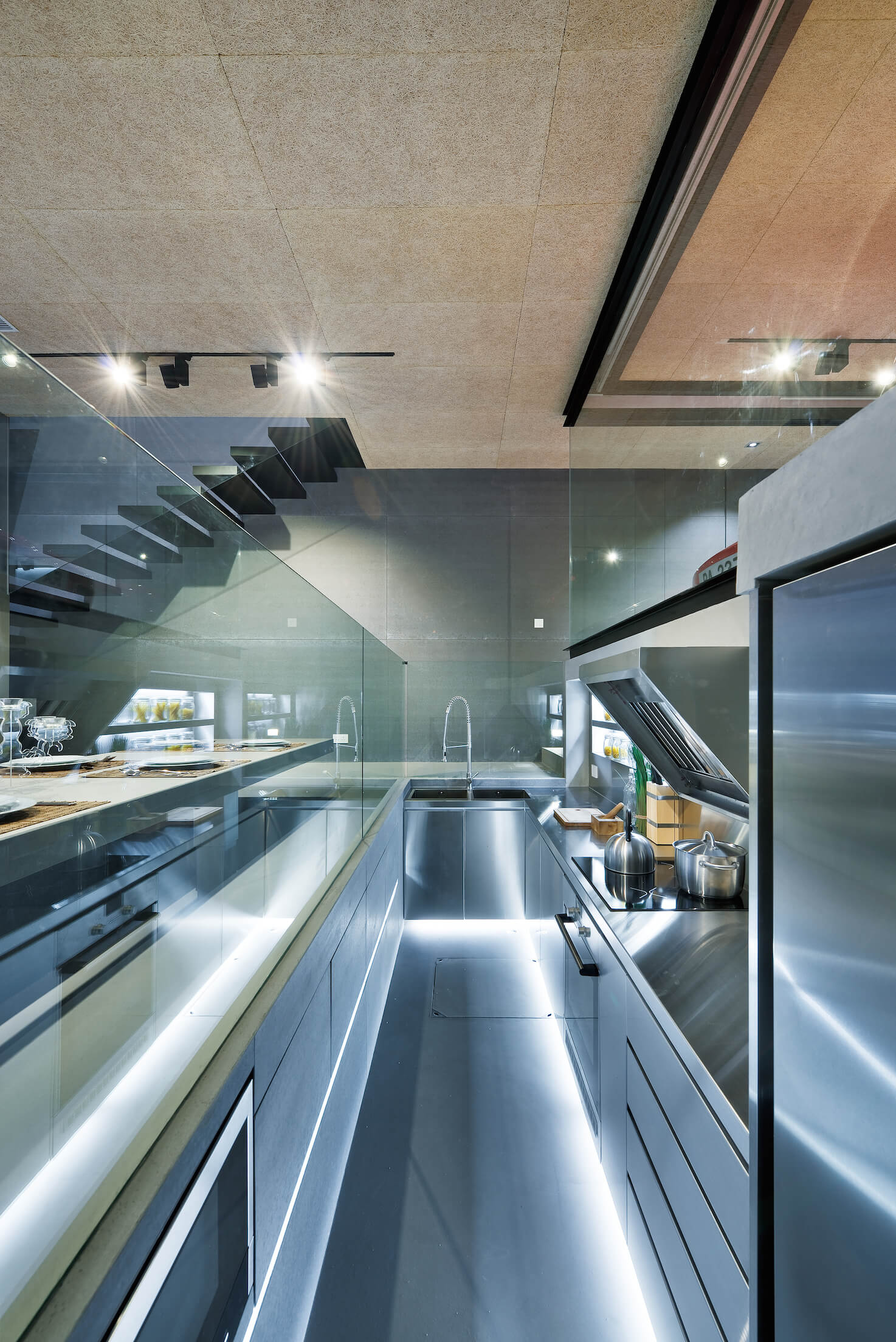 Close view of ultra-modern kitchen, utilizing novel sunken space, awash in brushed aluminum material.