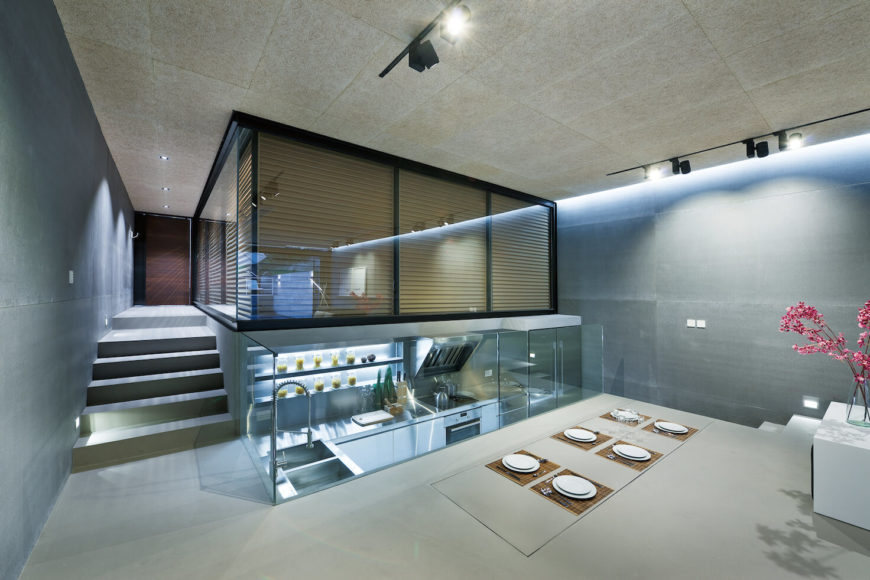 The home as seen with garage shades and dining table in closed position. Low glass wall separates kitchen space from main body, while steps to the right allow access.