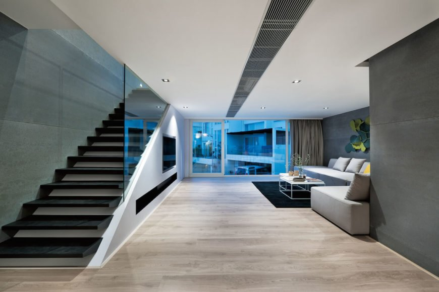 View down length of second floor space, with TV and media bar embedded in wall below staircase leading to upper level.