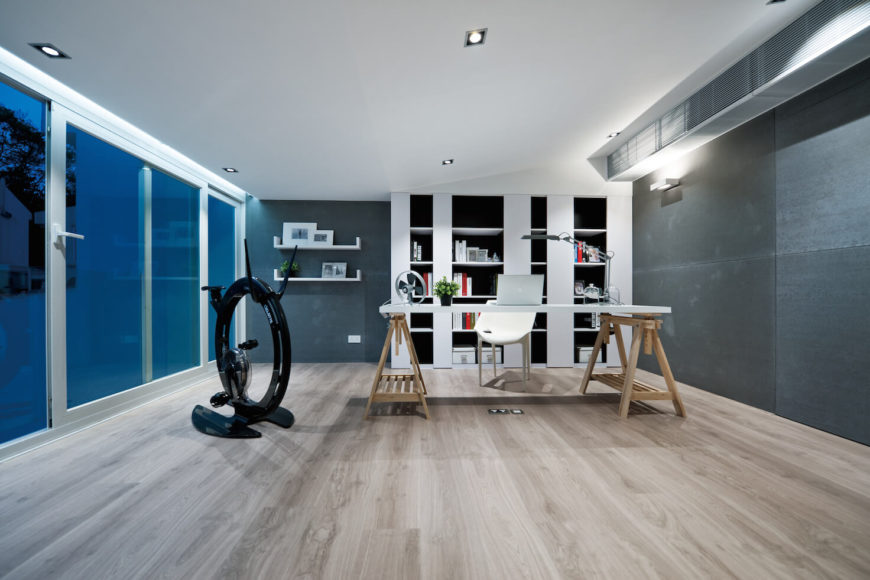 Top floor contains a full office space, with this unique white slab table sitting on natural wood sawhorses. White and black shelving built into far wall, large sliding glass door to balcony at left, and unique stationary cycle feature in this striking room.