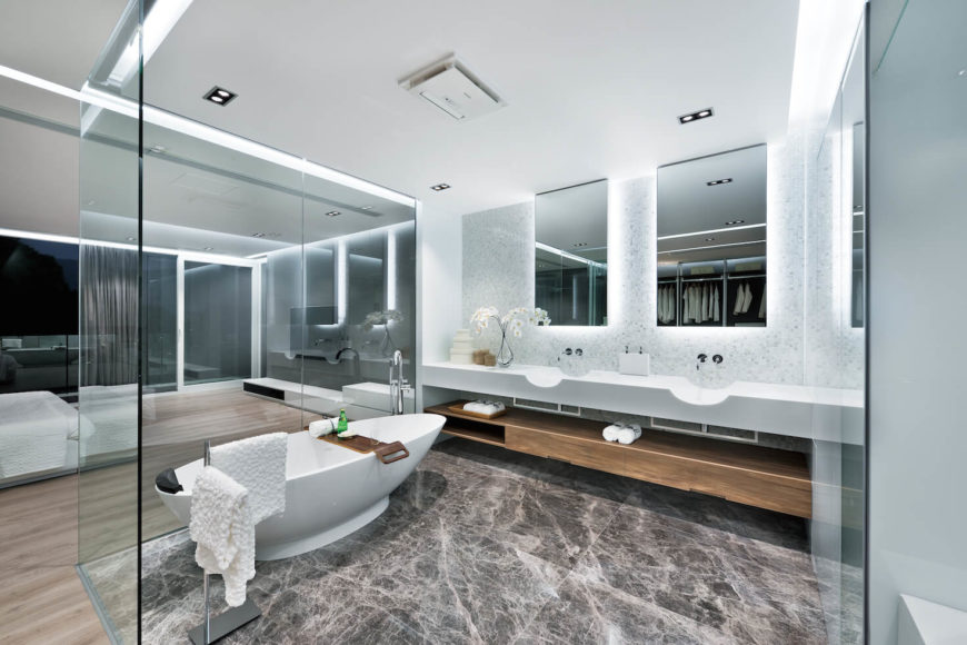 Dark marble floor bathroom contains white pedestal tub and natural wood storage below white twin vanities.