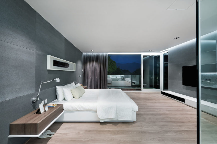 Primary bedroom features expansive views over glass-walled balcony, plus wall-mounted wood shelves flanking the white bed.