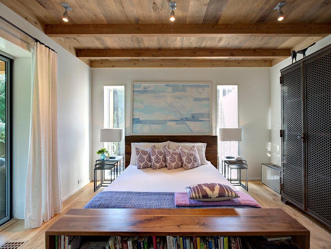 Primary bedroom features large natural wood book case standing at foot of the bed over more of the natural hardwood flooring. Large black wardrobe stands at right, with another sliding glass patio door on left.