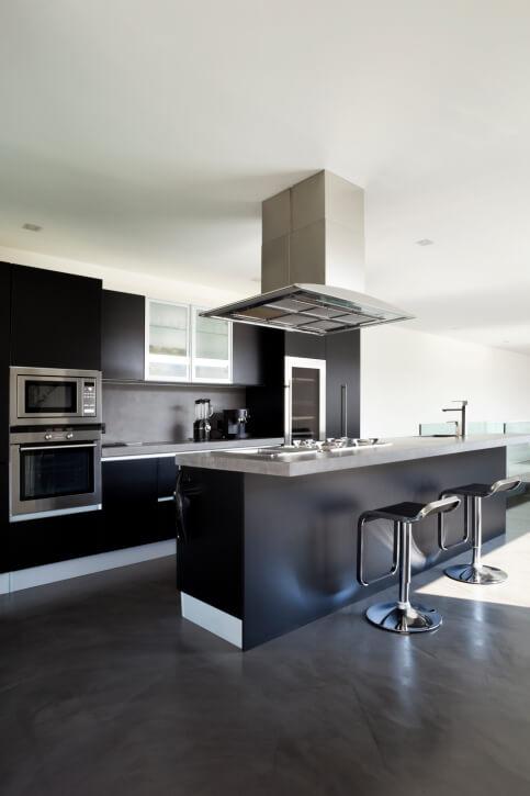 Modern kitchen design with black cabinetry on dark brown floor.