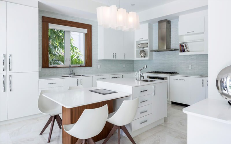 Kitchen features thoroughly modern appointments, including glossy white cabinetry and countertops, micro-tile blue backsplash, and two-part island featuring cabinetry, built-in sink, and lower dining space with natural wood structure.