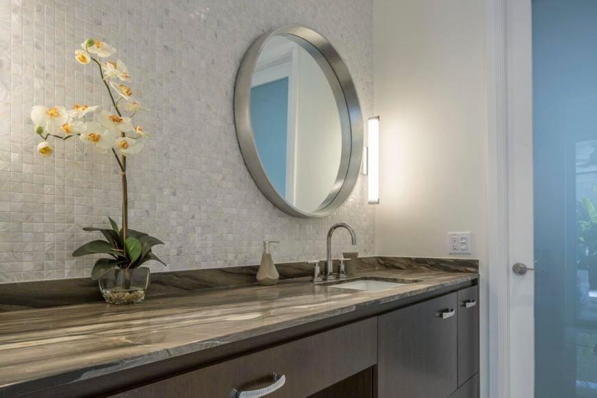 Bathroom features dark marble countertop over dark wood cabinetry, with light tile backsplash holding metallic framed mirror.