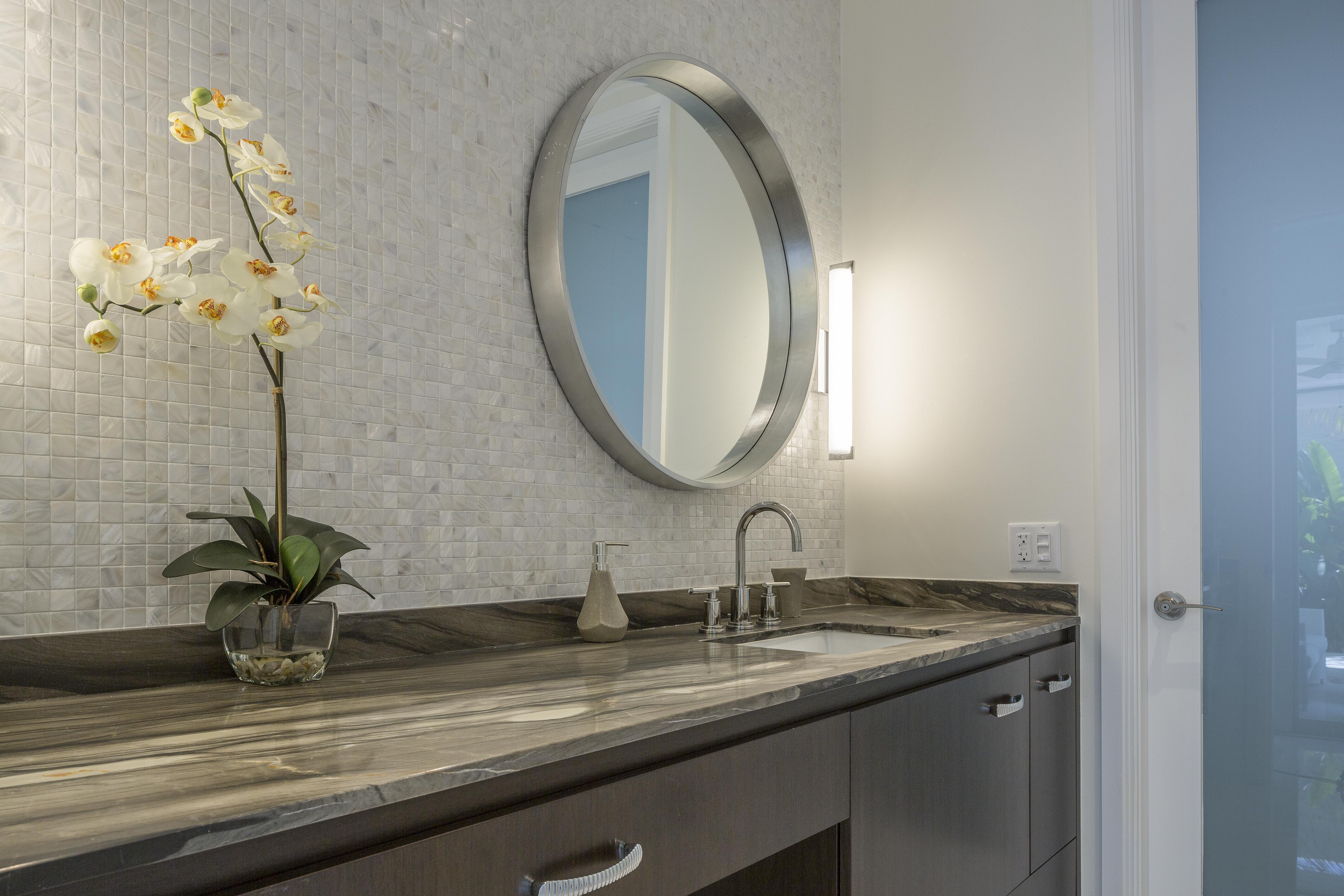 Bathroom features dark marble countertop over dark wood cabinetry, with light tile backsplash holding metallic framed mirror.