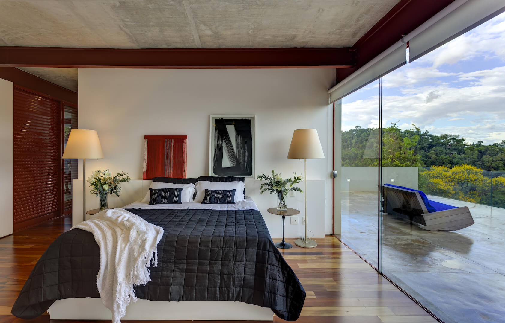 Primary bedroom suite on upper floor continues the natural hardwood flooring, with more art pieces standing on built-in wall shelf. Seamless glass door slides open to private balcony space with blue cushioned wooden rocking sofa.