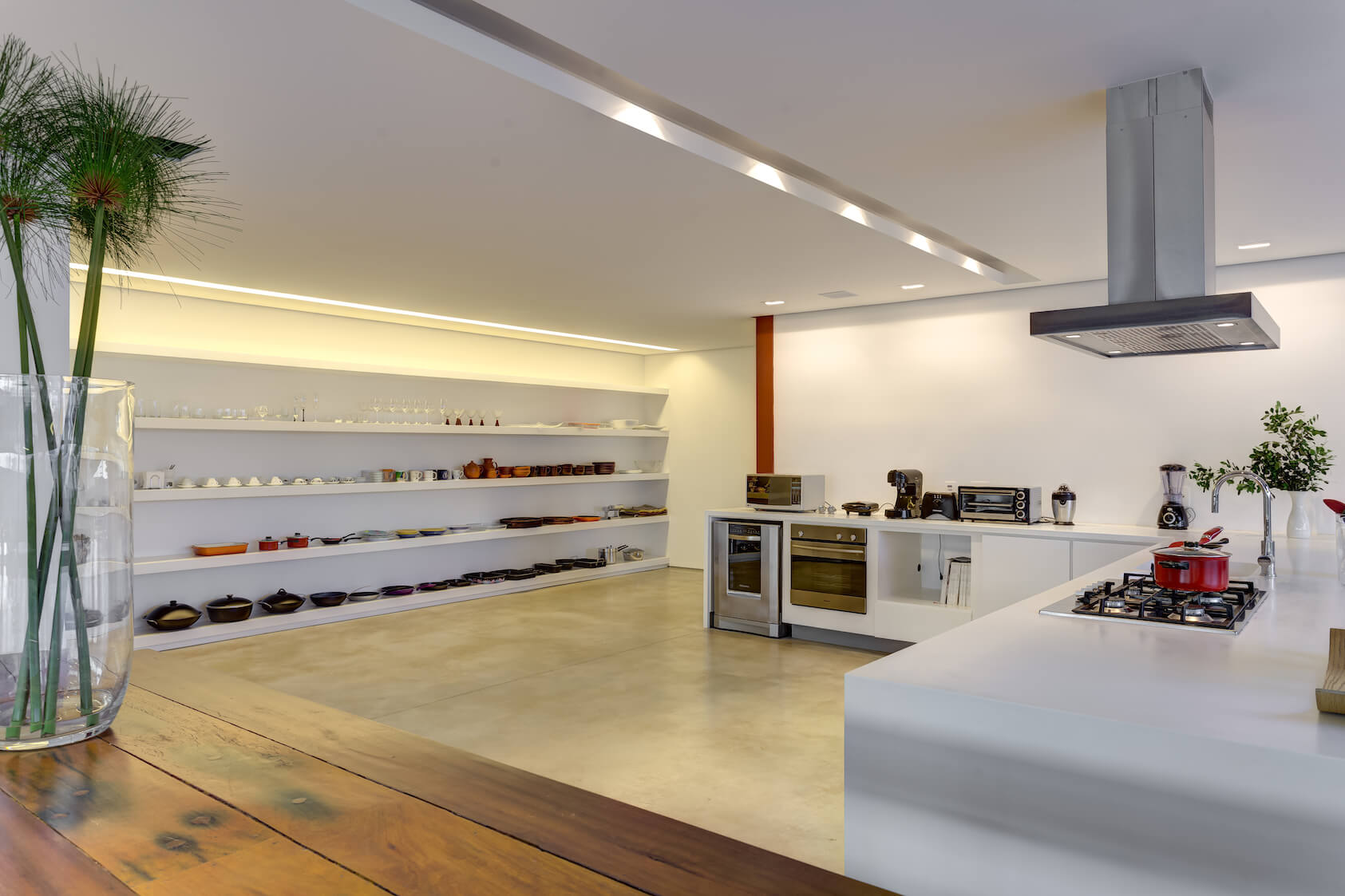 The thoroughly modern and minimalist kitchen space comprises a single large L-shaped island with white countertops, while all cooking utensils and dishes are kept in the open on an expanse of white shelving at left.